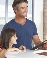 Father and daughter checking in at dental office reception desk