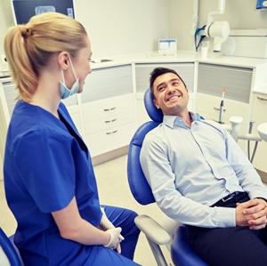 man in blue dress shirt smiling in dental chair