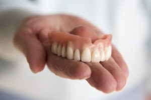 person holding dentures