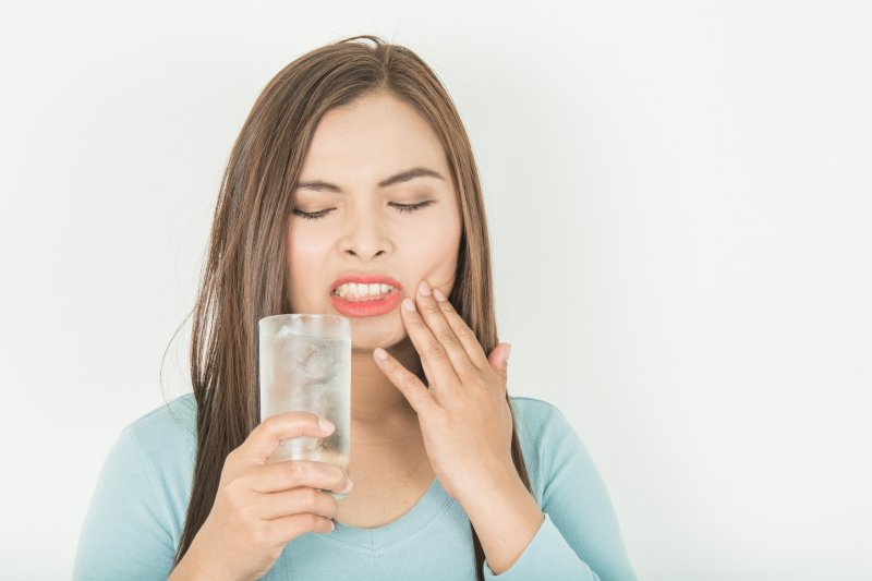 a woman holding a glass of water in one hand and her cheek in the other after experiencing tooth sensitivity